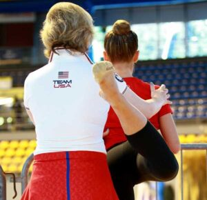A female coach adjusting a young gymnast's posture