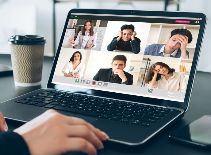 Photo of computer screen with 6 bored people in meeting
