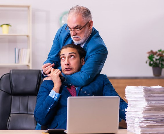 Older male boss trying to strangle younger male worker in an office setting