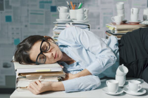 photo of businesswoman sleeping at desk surrounded by papers and coffee cups