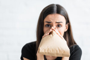 photo of scared-looking woman breathing into a paper bag
