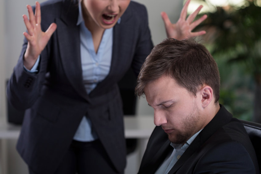 photo of boss yelling at employee who looks ashamed